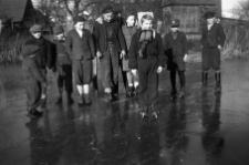 Dzieci na wiejskim stawie uczą się jeździć na łyżwach