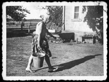 Lucyna Uzarek przy codziennych obowiązkach w obejściu gospodarskim. W tle kadź do zbierania wody deszczowej