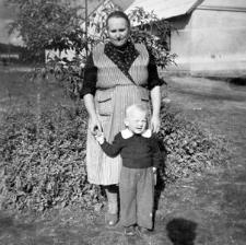 Maria Gliefe z wnukiem Janem na tle budynków mieszkalnych w Łupawie