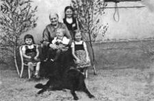 Dora Kabbe z babcią i młodszym rodzeństwem przed domem ozdobionym z okazji Zielonych Świątek