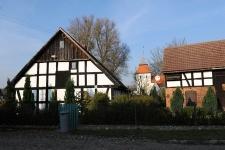 Budynek mieszkalny oraz gospodarczy z kościołem w tle w Swołowie